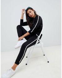 ASOS – Trainingsanzug mit Sweatshirt und Jogginghose mit Schnürung und Paspelierung - Schwarz