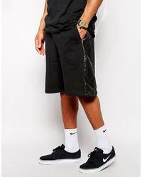 ASOS ASOS - Short oversize en jersey avec empiècements en PU sur les côtés - Noir