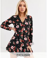 Boohoo Esclusiva - Vestito grembiule con bottoni nero a fiori e pois