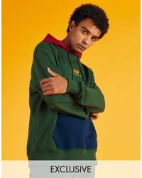 New Balance – er Kapuzenpullover mit Colourblock-Design und Logo – exklusiv bei ASOS - Grün