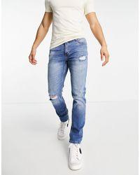 River Island – Schmale Jeans mit Zierrissen - Blau