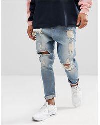ASOS Jeans lavaggio vintage azzurro con cavallo basso e strappi evidenti - Blu