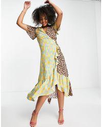 Never Fully Dressed Vestido semilargo cruzado con bajo con volantes y estampado - Amarillo