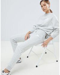 Nike Rally - Pantalon de jogging slim à logo virgule - Gris