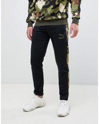 PUMA Pantalon de jogging avec rayure sur le côté motif camouflage - Noir