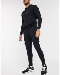 ASOS Survêtement composé d'un hoodie et d'un jogger cargo ajusté - Noir