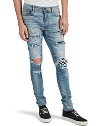 Amiri Art Patch Distressed Skinny Jeans - Blue