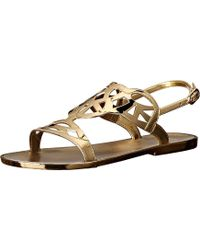e5f70797c4cec Lyst - Stuart Weitzman Gold Leather Itsybitsy T-strap Sandals in ...