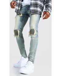 BoohooMAN Skinny Biker Jeans mit Stretch-Anteil, Rissen und Flicken - Blau
