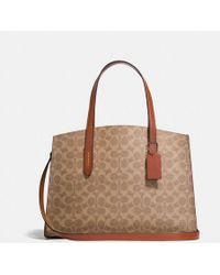 COACH Charlie Carryall In Signature Canvas - Brown