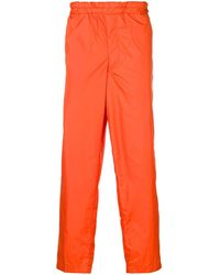Comme des Garçons Pantaloni sportivi con bande laterali - Arancione