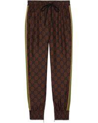 Gucci Pantalon en soie à imprimé GG Supreme - Marron