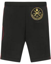 Vetements Shorts neri elasticizzati con stampa gialla e logo sur tone sul fronte, linee rosse ai lati. - Nero
