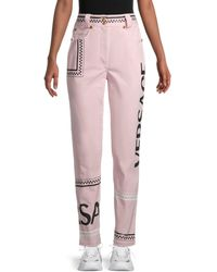 Versace High-rise Logo Graphic Denim Trousers - Pink