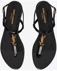 Saint Laurent Cassandra Flat Sandals In Patent Leather With Gold-tone Monogram - Black