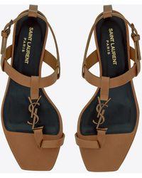 Saint Laurent Flache cassandra sandalen aus glattleder mit goldfarbenem logo - Natur