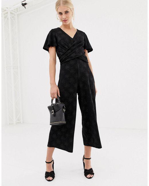 Tuta jumpsuit nera con glitter e incrocio sul davanti di Oasis in Black