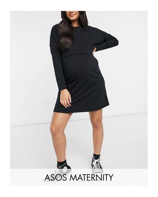 Esclusiva ASOS DESIGN Maternity - Vestito T-shirt corto a maniche lunghe nero con strato sovrapposto per l'allattamento di ASOS in Black