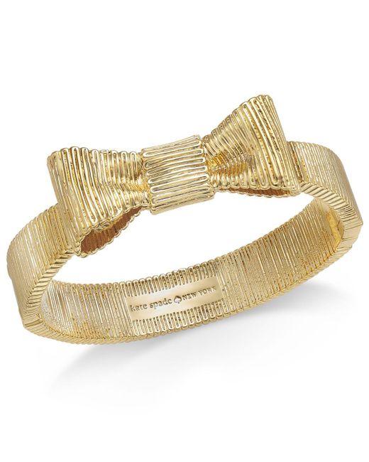 Kate Spade | Metallic Gold-tone Engraved Bow Bangle Bracelet | Lyst