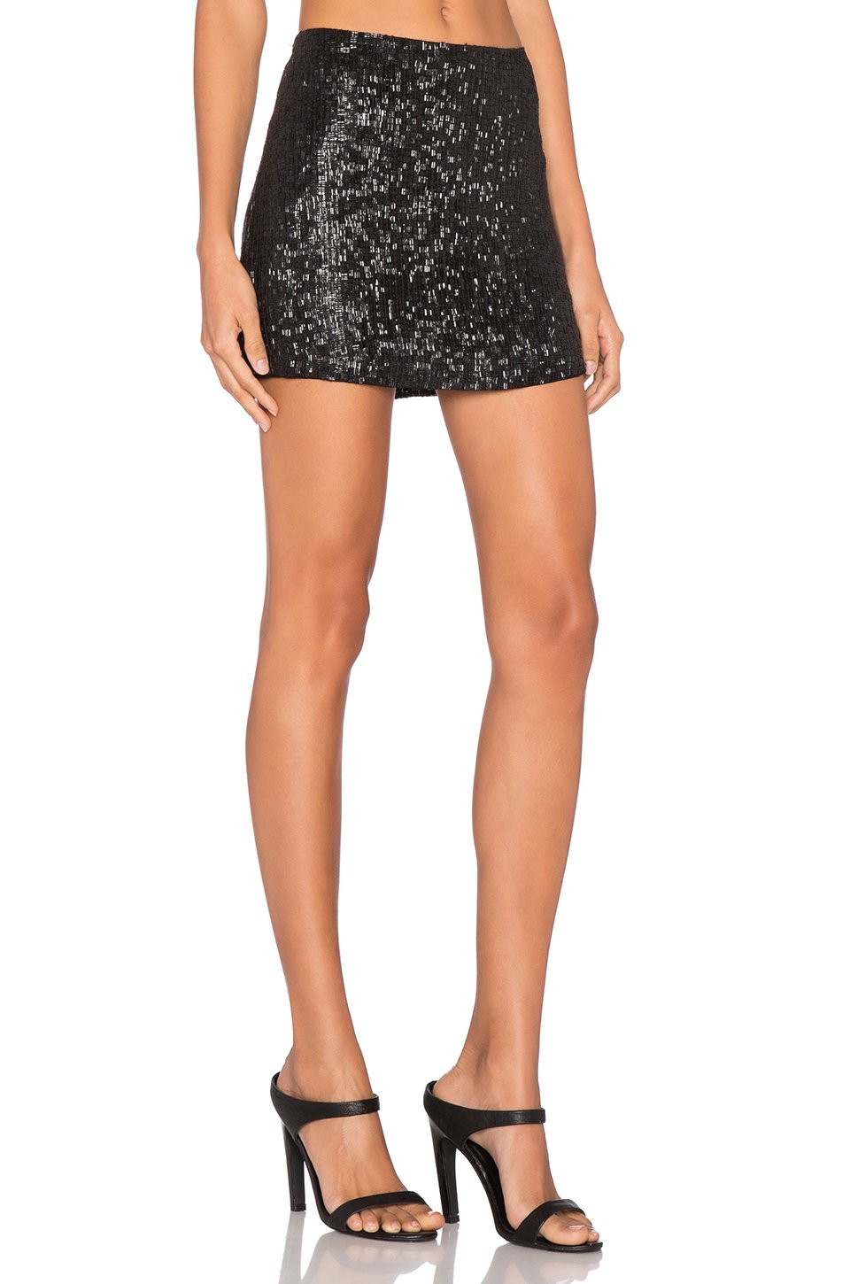A black Alex Evenings plus size sequin skirt, worn with a white tunic-style top and black waist ribbon, is classic and elegant. Strappy heels and some colorful bracelets add detail to the look, or wear with embellished black pumps and a loose hairstyle to keep the look casual.