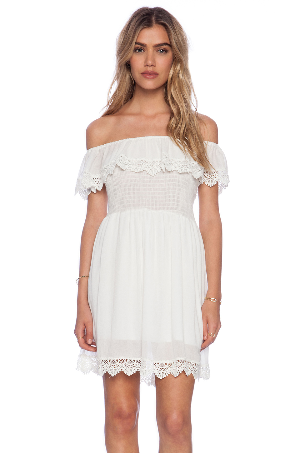 Floral lace adorns this piece with a flutter hem Read More This white mini dress gives a cheeky fit perfectly made to layer or wear alone for a romantic feel. Floral lace adorns this piece with a flutter hem and halter fit for the perfect support.