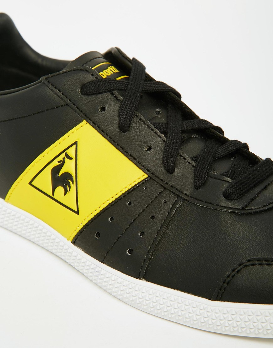 le coq sportif portalet trainers black in yellow for men. Black Bedroom Furniture Sets. Home Design Ideas