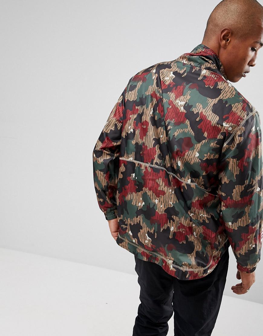 eefe579e2663c Adidas Originals - Red X Pharrell Williams Hu Hiking Half Zip Windbreaker  In Camo Print Cy7871