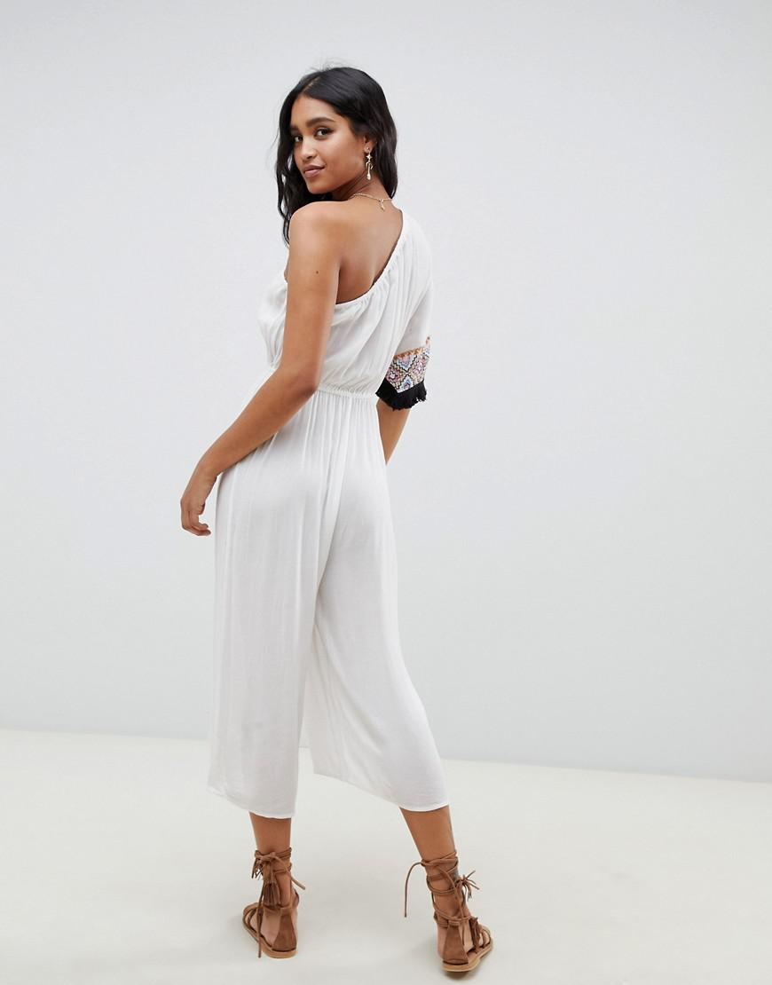 8b8f257867 Lyst - ASOS Embroidered Fringed Tape One Shoulder Beach Jumpsuit In White  in White