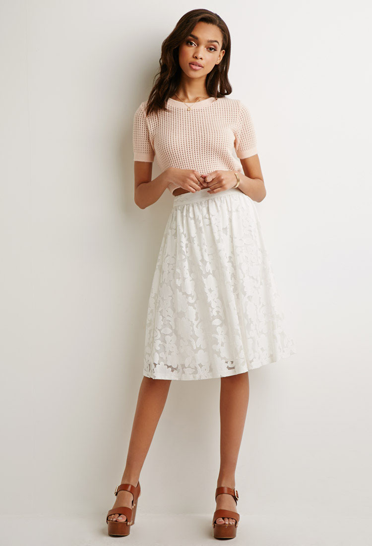 This short A Line skirt is white, with a black floral design. The skirt is lined, so that there is a soft, smooth feeling next to the skin. The natural waist line allows the skirt to flow casually around the legs, and the invisible zipper at the back allows for ease of putting on and taking off the skirt.