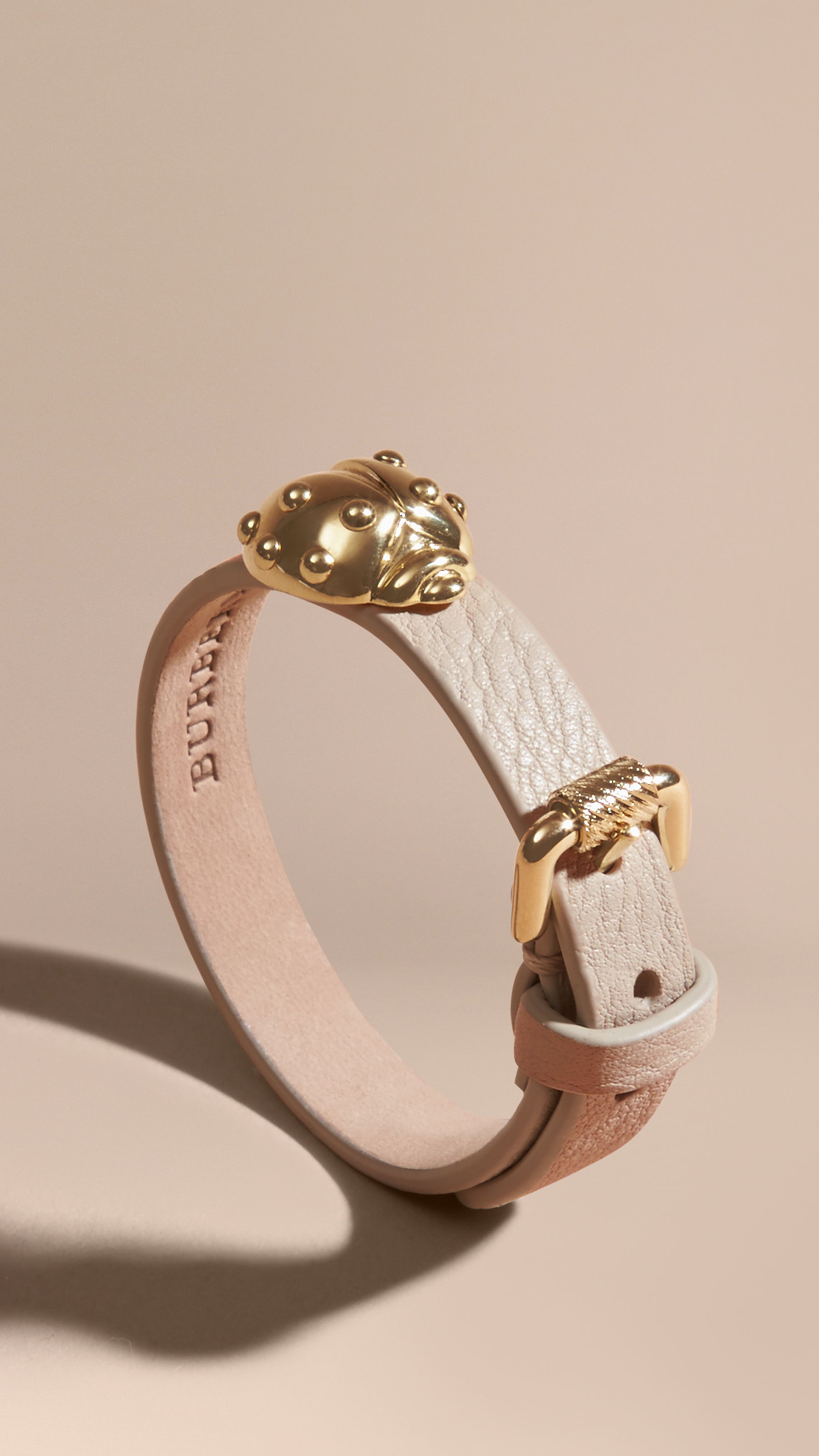 burberry ladybird motif leather cuff in gold