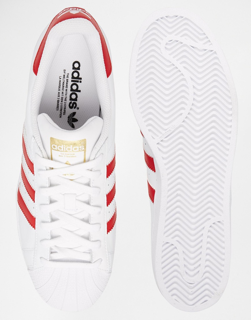 white adidas trainers with red stripes