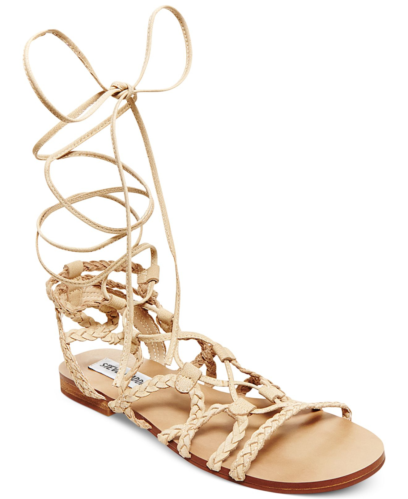 Intricate cutouts are pulled together by a lace-up front on a soft faux suede gladiator sandal.