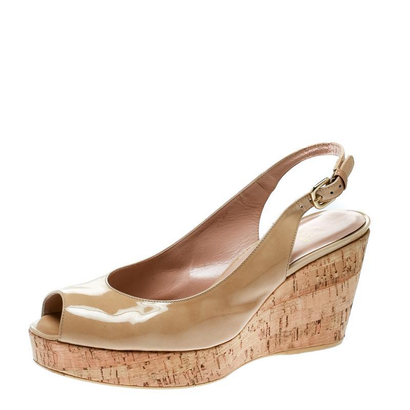 7a3d4904dfaf Stuart Weitzman. Women s Natural Patent Leather Jean Peep Toe Cork Wedge  Slingback Sandals