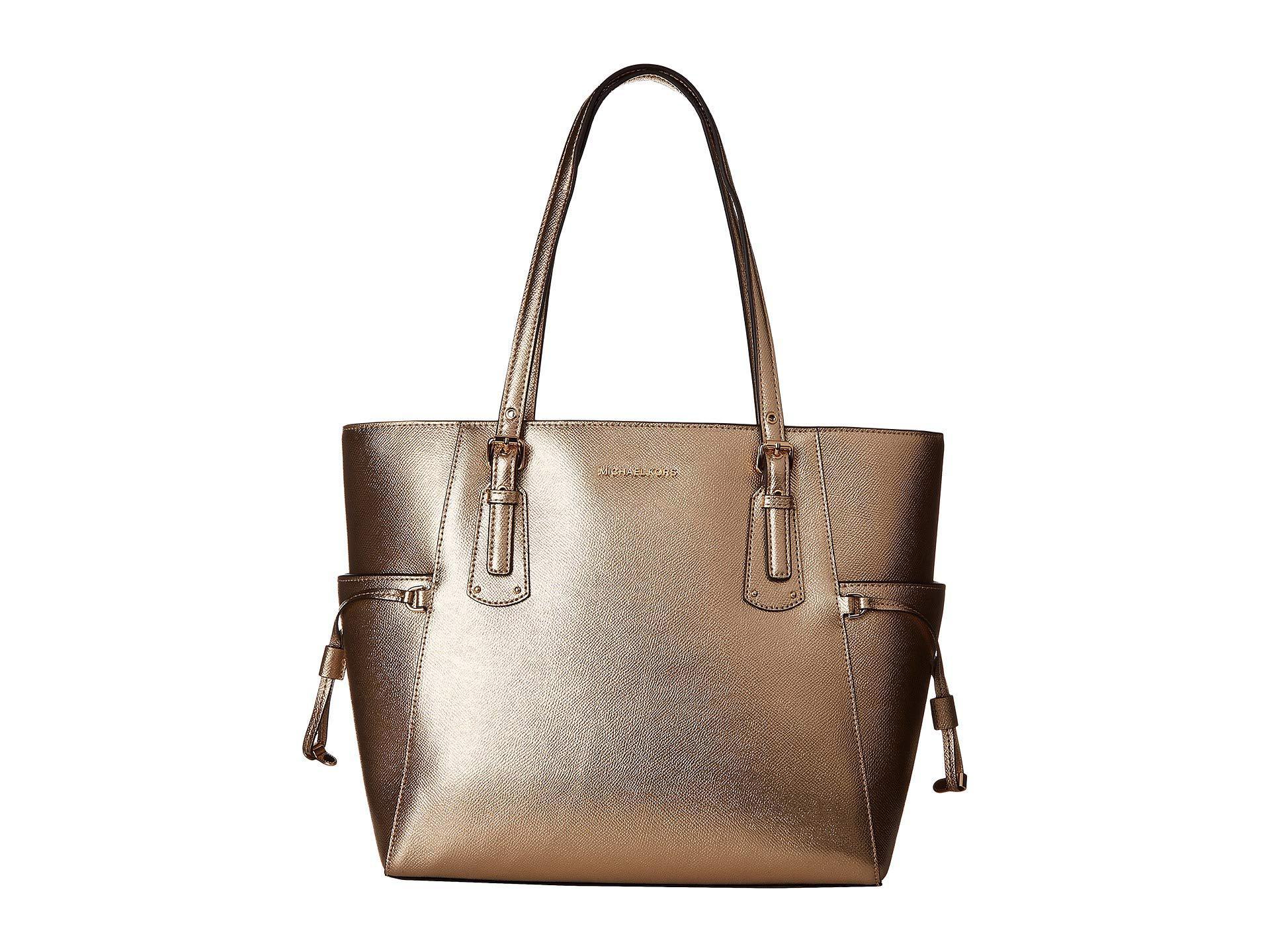 c7786bb592365 MICHAEL Michael Kors. Women s Metallic Voyager East west Tote (pale Gold) Tote  Handbags